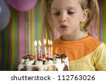 Happy children with birthday cake on a striped background - stock photo