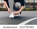 slim girl tie shoelaces on her... | Shutterstock . vector #1127787002