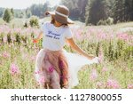 the girl in the hat runs across ... | Shutterstock . vector #1127800055