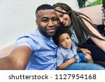young family taking a selfie... | Shutterstock . vector #1127954168