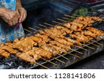 Small photo of moo ping, grilled pork skewer sticks on the bbq grill outdoor, Thai street food