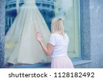 woman looking at the window... | Shutterstock . vector #1128182492