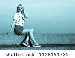 blond girl in denim skirt ... | Shutterstock . vector #1128191735