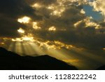 sunbeams in the clouds before... | Shutterstock . vector #1128222242