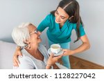 health visitor and a senior... | Shutterstock . vector #1128227042