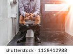 man sitting on a toilet seat | Shutterstock . vector #1128412988
