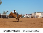 a cowboy competing in a bull... | Shutterstock . vector #1128623852