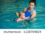 swimming instructor teaches... | Shutterstock . vector #1128704825