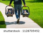 Father Carrying Twin Babies In...