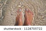 women's feet splashing in sea... | Shutterstock . vector #1128705722