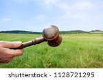 wooden gavel in a hand on the... | Shutterstock . vector #1128721295