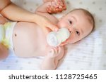 mother feeding her child from a ... | Shutterstock . vector #1128725465
