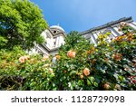 Stock photo st paul s cathedral in london uk during summer with pink orange roses in green garden closeup 1128729098