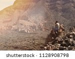 man sitting in the rocks and... | Shutterstock . vector #1128908798