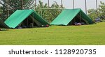two green tents mounted in a... | Shutterstock . vector #1128920735