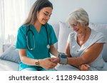 caregiver measuring blood... | Shutterstock . vector #1128940388