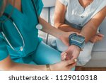 happy nurse measuring blood... | Shutterstock . vector #1129010318