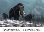 A trio of woolly mammoths trudges over snow covered hills.  Behind them, mountains with snow covered peaks rise above dark green forests of fir trees. 3D Rendering