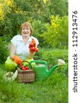 Happy mature woman with vegetables harvest - stock photo