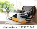 Small photo of Open yellow suitcase with different clothes packed for journey at home