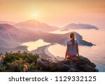 young woman sitting on the top... | Shutterstock . vector #1129332125
