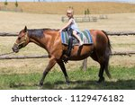 a young girl walks on a trained ... | Shutterstock . vector #1129476182