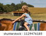 a young girl walks on a trained ... | Shutterstock . vector #1129476185