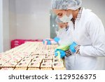 confectioners in white uniform... | Shutterstock . vector #1129526375