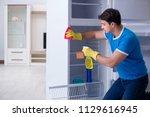 man cleaning fridge in hygiene... | Shutterstock . vector #1129616945