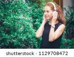 beautiful women are listening... | Shutterstock . vector #1129708472
