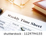 weekly time sheet and pen on an ... | Shutterstock . vector #1129794155