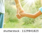 hands of parent and child in... | Shutterstock . vector #1129841825