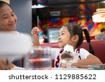 asian mom and daughter in ice...   Shutterstock . vector #1129885622