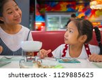 asian mom and daughter in ice...   Shutterstock . vector #1129885625