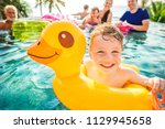 boy swimming in a pool with... | Shutterstock . vector #1129945658