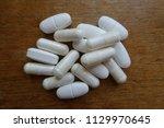 handful of white caplets of... | Shutterstock . vector #1129970645