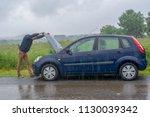 car trouble in the rain. broken ... | Shutterstock . vector #1130039342