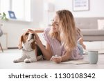 young woman with her dog at home | Shutterstock . vector #1130108342