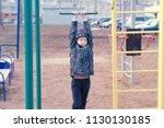 boy swings on a gymnastic... | Shutterstock . vector #1130130185