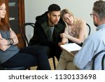 a young couple talking to a... | Shutterstock . vector #1130133698