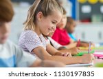 Small photo of Smiling scholar girl sitting with other children in classroom and writing on textbook. Happy student doing homework at elementary school. Young schoolgirl feeling confident while writing on notebook.