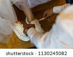 bridegroom helps the bride put... | Shutterstock . vector #1130245082