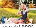 schoolgirl in uniform joyful... | Shutterstock . vector #1130308886