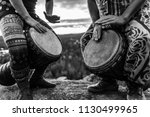 Man and woman playing djembe on the top of a mountain, black and white