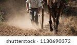 farmer and horse plowing farmer ... | Shutterstock . vector #1130690372