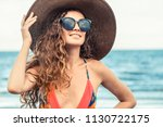 happy young woman wearing... | Shutterstock . vector #1130722175