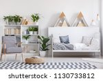 patterned armchair next to pouf ... | Shutterstock . vector #1130733812