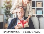 young daughter gives her father ... | Shutterstock . vector #1130787602