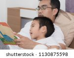 Small photo of Asian young fathers read fable books to his son while lying in bed