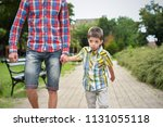 father holding hand with son in ... | Shutterstock . vector #1131055118